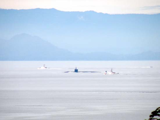 Nuclear submarine being escorted by two Coastguard gunships.