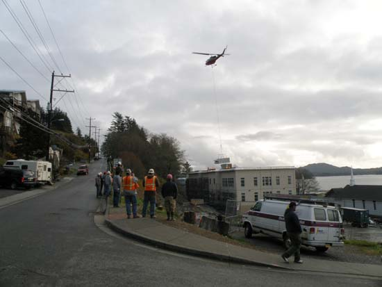 Helicopter lifting an AC unit into place.